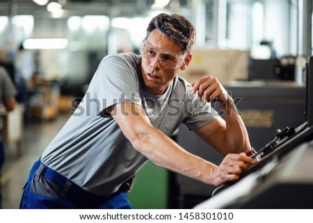Manual worker working at CNC machine and contemplating in a factory.