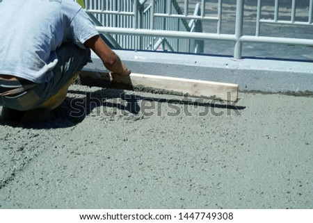 manual worker working on smooth concrete on driveway