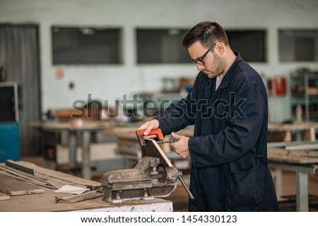 Manual worker working with bench hold fast at metal industry.