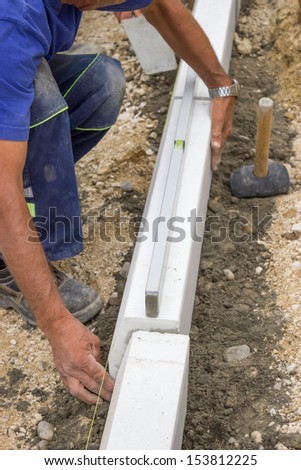 manual worker works with a level, worker leveling concrete curbs of new sidewalk