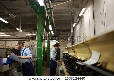 Manual workers in overalls working on lathes for printing papers in the printing plant