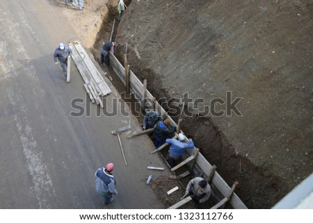 Manual workers mount span of bridge on the roadway