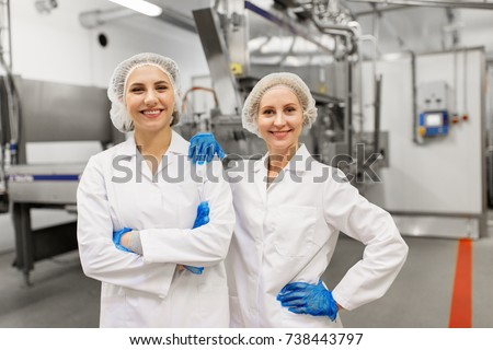 manufacture, industry and people concept - happy women technologists at ice cream factory shop #738443797