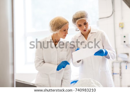 manufacture, industry, food production and people concept - women technologists with paper and powdered milk at ice cream factory shop