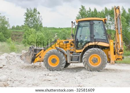 Manufactures excavator digging- yellow vehicle