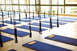 Many aerial yoga exercise equipment with blue cushions in gym for aerial silk (yoga fly) for background or texture - new trend of exercise concept.