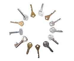 Many assorted old multi-colored metal antique keys of different shapes laid out in circle isolated on white background. Home security concept. Copy space for text.