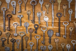 Many assorted old multi-colored metal antique vintage keys of different shapes on wooden scratched table background. Home security concept.