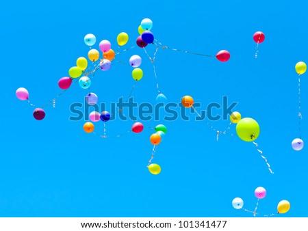 Many balloons fly into the blue sky
