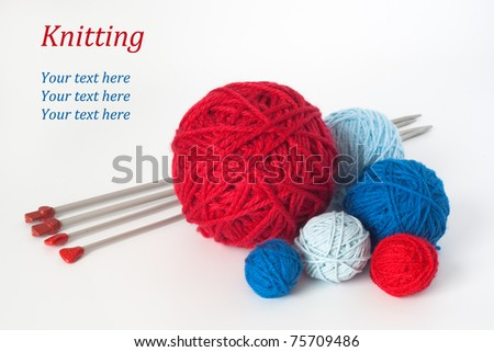 Many balls of blue and red colors for the knitting, and two pairs needle