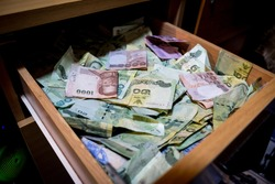 Many banknotes are inside the drawer.