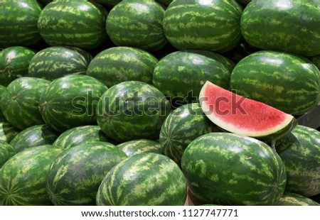 Many big sweet green watermelons and one cut watermelon at fruit market