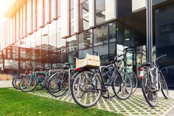 Many bike parked near modern apartment residential buiding or college campus at downtown of european city street. Eco-friendly transport and healthy active lifestyle concept. Sustainable work commute