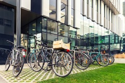 Many bikes parked near modern apartment residential buiding or college campus at downtown of european city street. Eco-friendly transport and healthy active lifestyle concept. Sustainable work commute