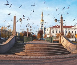 Many birds over the ancient bridge over the canal and the church in the autumn park