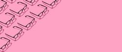 Many black trendy eyeglasses on pastel pink background. Repetitive pattern border frame. Minimal hipster eyewear concept. Copy space.