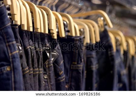 Many blue denim jeans on coat hanger