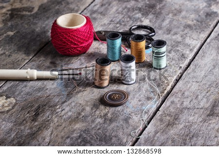 Many bobbin of thread with needle and button on table