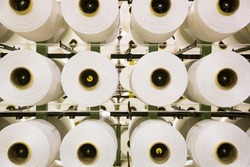 Many bobbins with white threads are used in the production of fabric
