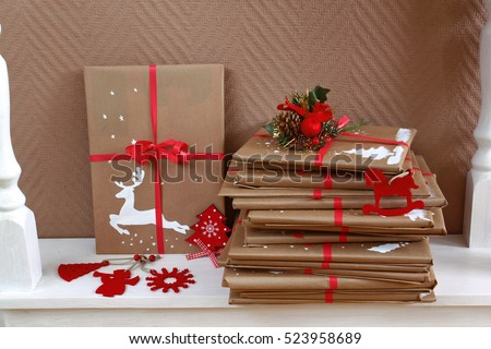 Many books as Christmas gifts, wrapped and homemade decorated, piled on white wooden console table. Handmade painting of deer on a parcel. Side view.