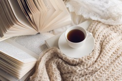 Many books  on the bed and a cup of coffee.