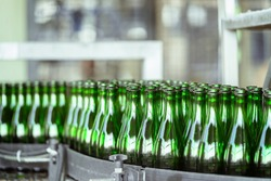Many bottles on conveyor belt in factory