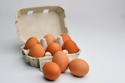 Many brown eggs isolated on white. Chicken eggs are fresh in a cardboard package made of recycled waste paper. Fresh organic chicken eggs in carton pack or egg container.