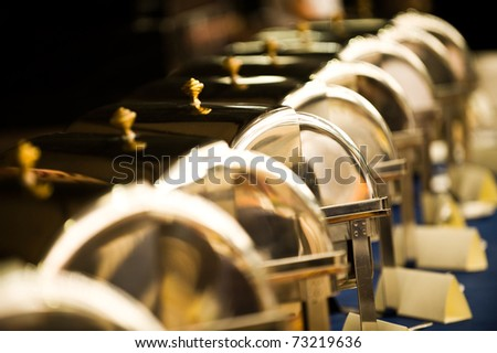 Many buffet heated trays ready for service, blue tone.