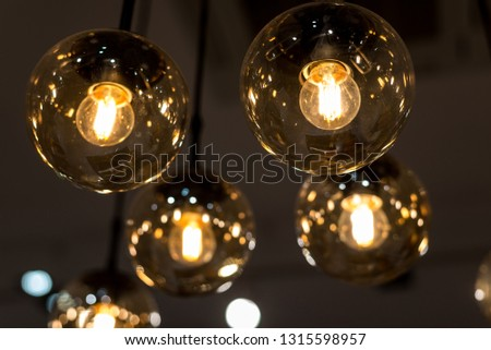 many burning incandescent bulbs hanging on the ceiling. Horizontal frame