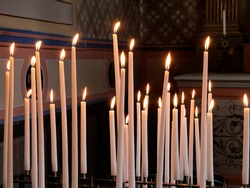 Many burning wax candles in a church