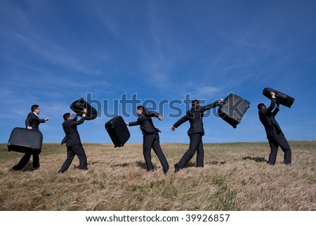 many businessman in the field walking with his luggage