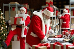 Many busy Santa Clauses packing gift boxes preparing fast xmas delivery. Three funny Santas walking in workshop warehouse in Merry Christmas rush delivering presents during holiday preparations.