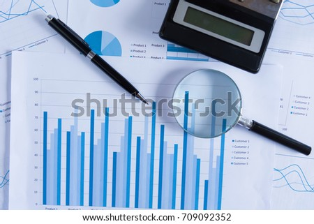 Many charts and graphs with magnifying glass and many pencil. Reflection light and flare. Concept image of data gathering and statistical working. #709092352