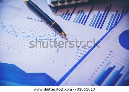 Many charts and graphs with magnifying glass and many pencil. Reflection light and flare. Concept image of data gathering and statistical working. #781051813