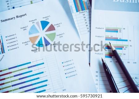 Many charts and graphs with pen-pencil. Reflection light and flare. Concept image of data gathering and statistical working.  #595730921
