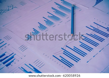 Many charts and graphs with pen-pencil. Reflection light and flare. Concept image of data gathering and statistical working. #620058926