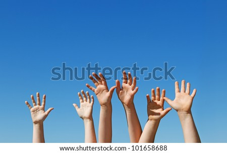Many children hands raised up against the blue sky with copy space