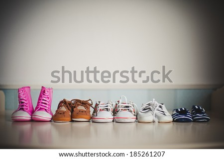 many children\'s shoes standing in a row on the table