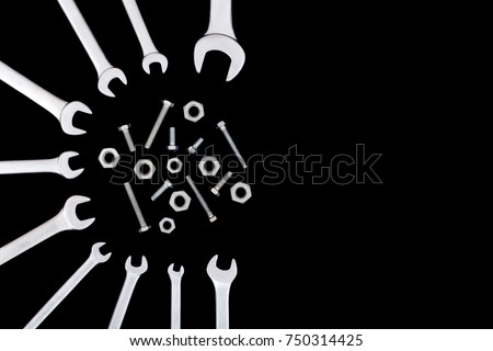Many chrome-plated spanners around screws, bolts and nuts. Spanners with space for text on a black background.
