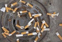 Many cigarette butts discarded on a drain