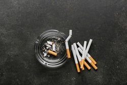 Many cigarettes and ash tray on dark background