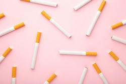 Many cigarettes on a pink background. Top view.