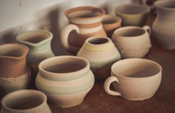 Many clay pot is on the table in pottery. Bright pottery. Many white, not painted clay pottery standing on wooden table. Creative studio potter. Workplace wizard Crock pottery