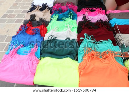 many clothes with many colors for sale at outdoors market on the street