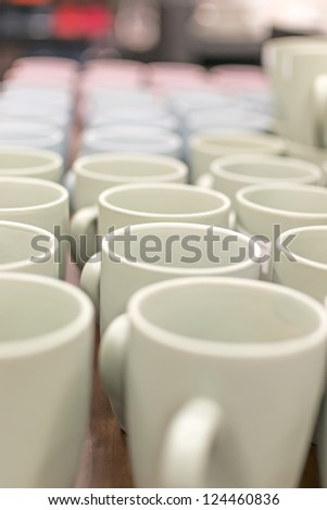 Many coffee mugs in a line over a buffet