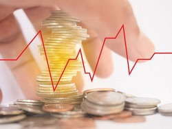 Many coins are stacked up. There is spread beside And with the hands of people going to catch the white background with a red line graph Blackline grid concept finance, investment, COVID-19 effects
