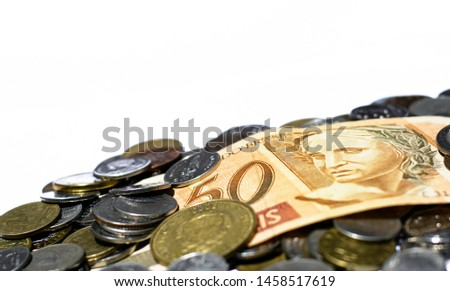 Many coins from many country and Brazilian currency,money isolated on white background.Focus on eye of a man on banknote