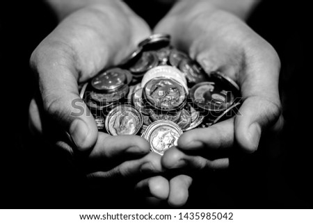 Many coins from many country in a hands on black and white color with black background,copy space