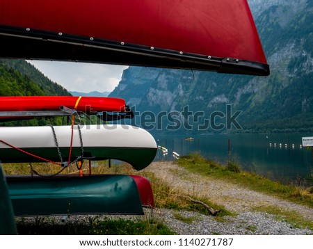 many colored canoes stored at a renting place at a swiss mountain lake