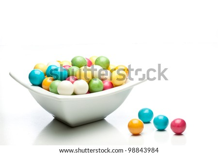 many colored gumballs on a white background